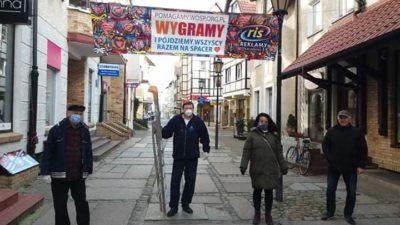 """Baner WOŚP nad ul. Mariacką. """"WYGRAMY i pójdziemy wszyscy razem na spacer"""""""